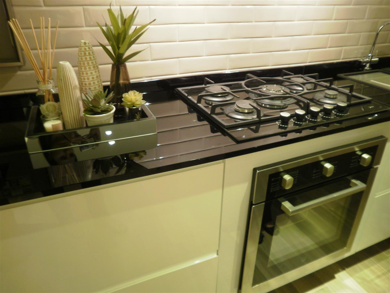 Móveis brancos e bancada preta na cozinha do Estúdio Nova Iorque  #8F753C 1440x1080 Banheiro Com Bancada Preta